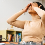 Stressed woman at her desk covering her eyes