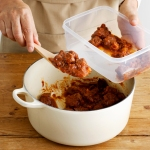 Hands putting leftover meat sauce in Tupperware