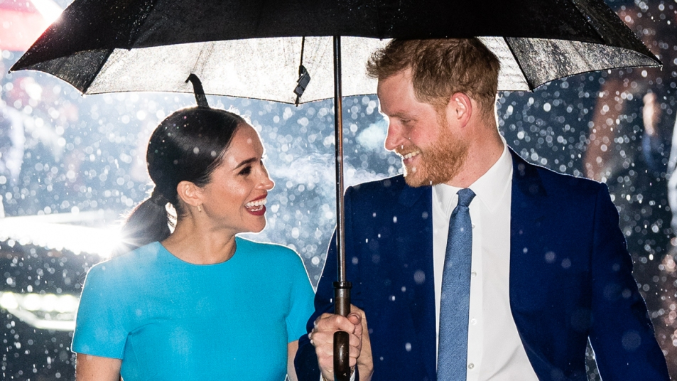 Prince Harry and Meghan Markle smiling at each other under an umbrella