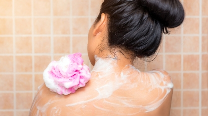 Back of woman using pink loofa in shower