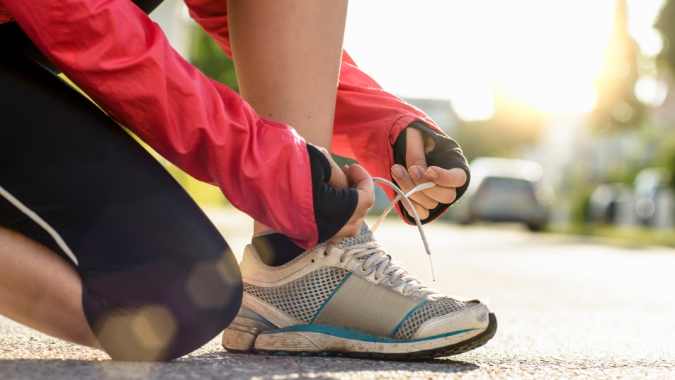 Woman's hands lacing up old sneakers