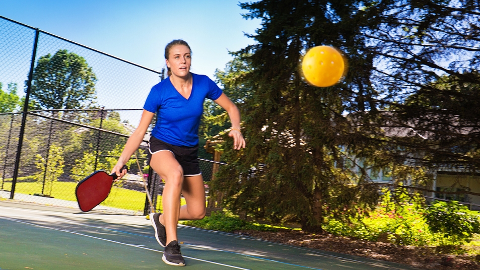 Woman in blue shirt playing pickleball