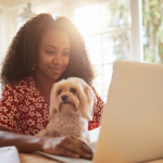 woman with dog typing on laptop
