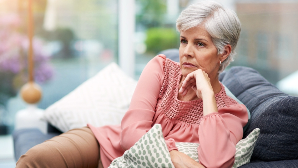 Woman looking angry sitting on a couch