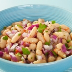 Bowl of cannellini beans with red onions and cilantro