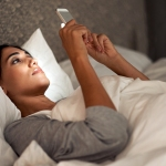 Woman in bed staring at her phone