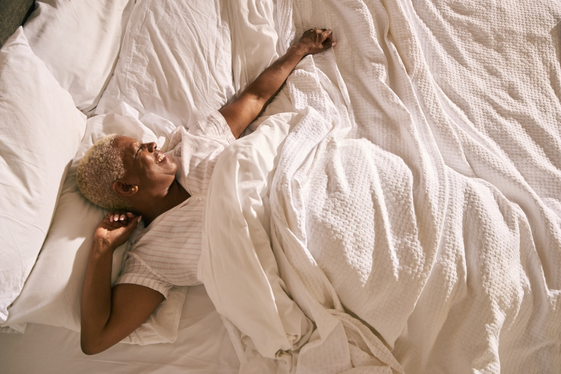 mature black woman wakes up and stretches in early morning light