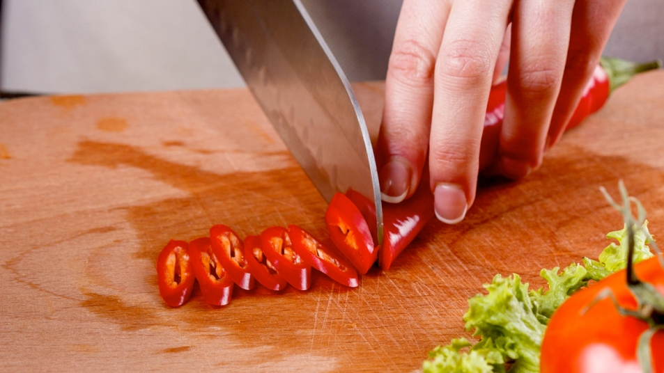 Woman's hands slicing red hot pepper