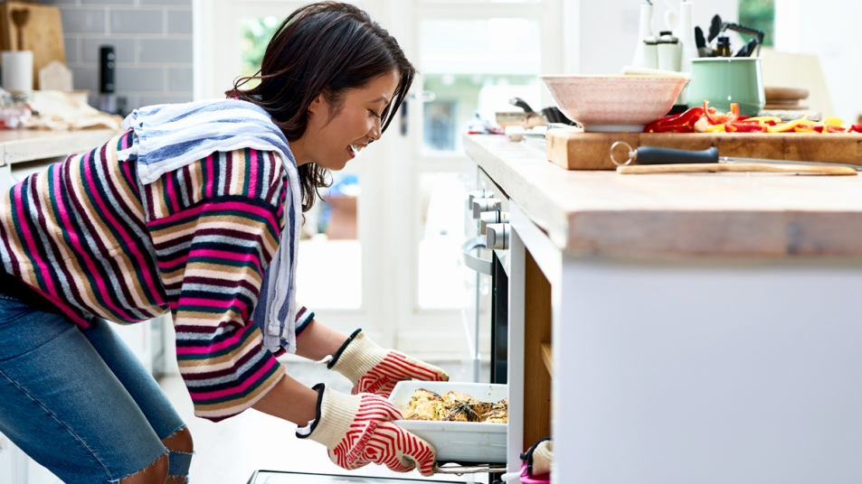 Woman pulling dish out of oven