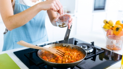 Woman adding spice to pan