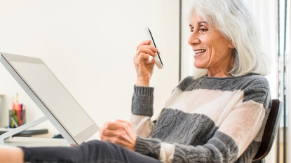 Woman with gray hair using phone speaker