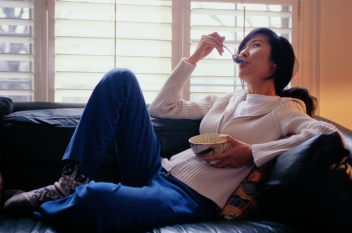 woman eating ice cream on the couch
