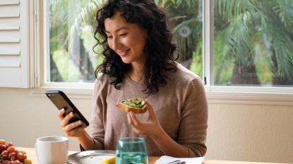 Woman eating avocado toast and looking at her phone