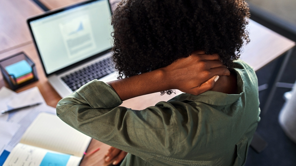 Woman at computer holding back of her neck