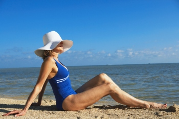 Mature woman sitting on beach.