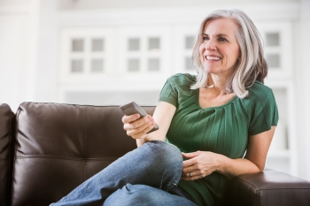 caucasian woman watching TV on sofa