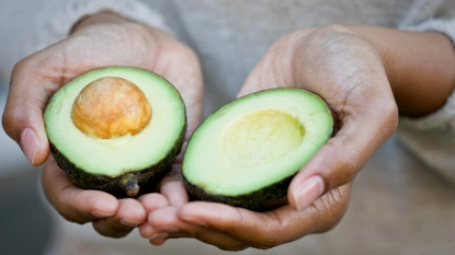 Hands holding a halved avocado