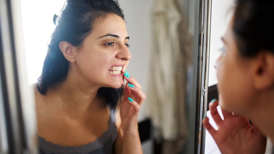 Woman looking at her teeth in a mirror