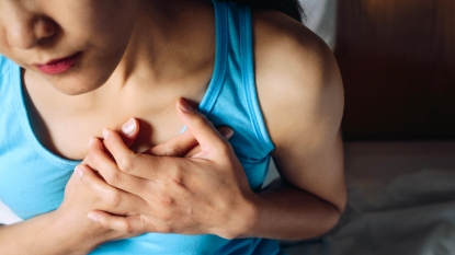 Woman in blue tank top clutching her heart