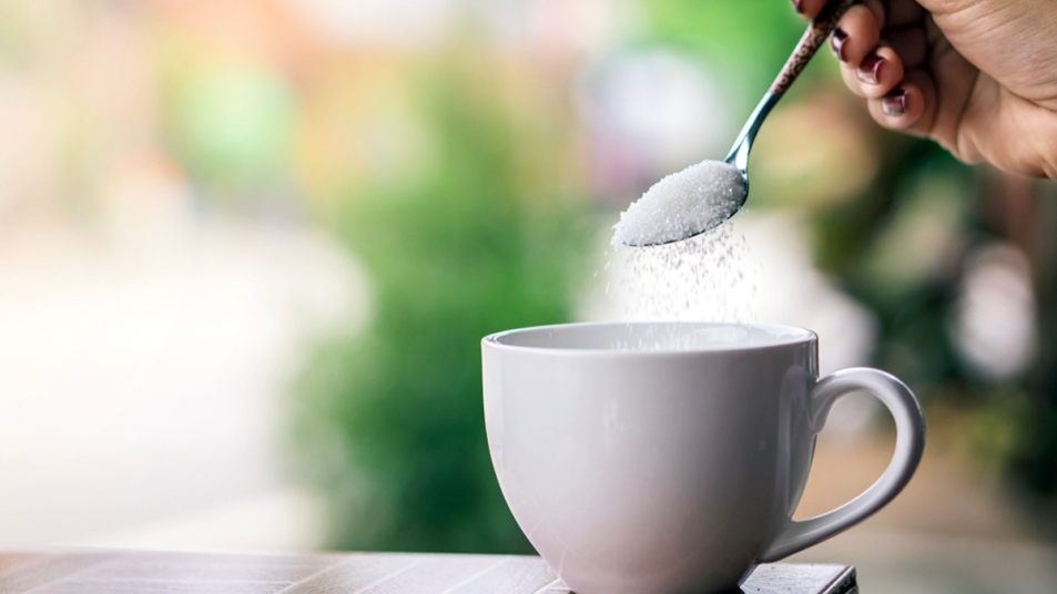 Pouring spoonful of sugar in coffee