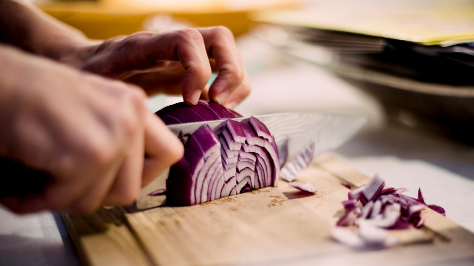 Hands with knife chopping red onion