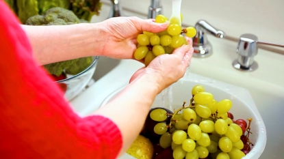 Woman's hands washing grapes in sink