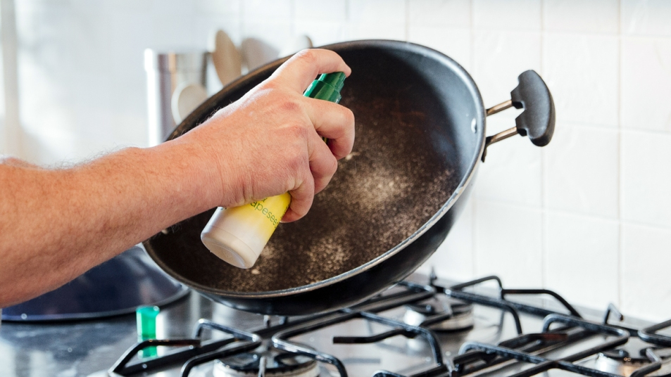 Hand spraying a pan with cooking spray