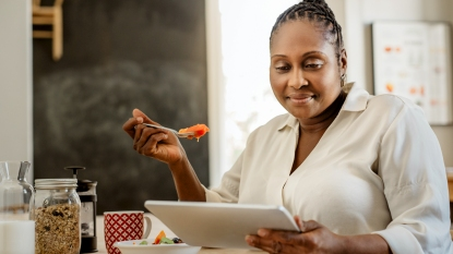Woman eating and reading a tablet