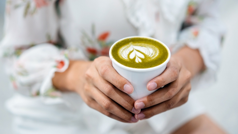 Woman holding cup of green tea