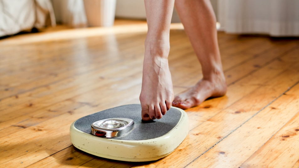 Woman's feet stepping on scale