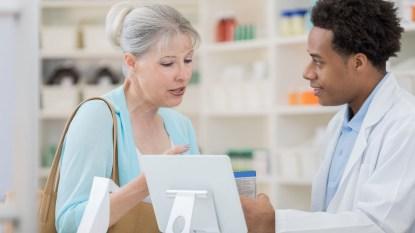 Senior woman asks pharmacy technician about medication