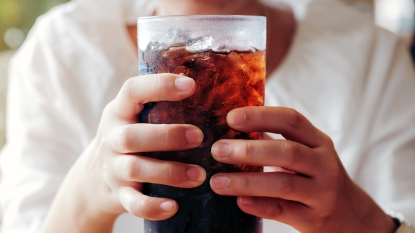 Hands holding glass of soda