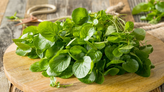 Watercress on a wooden cutting board