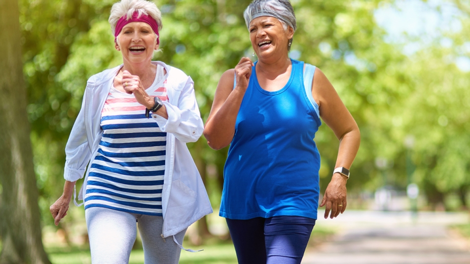 Two older women in workout clothes walking