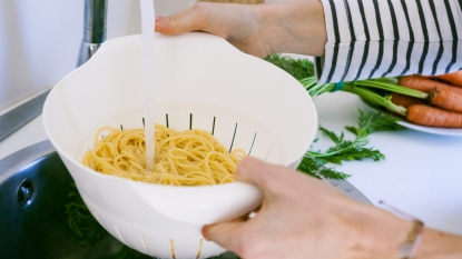 Woman rinsing pasta under tap
