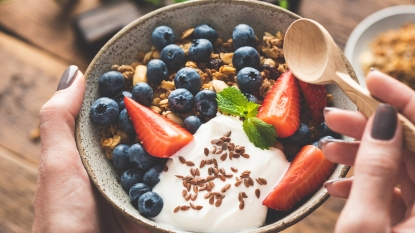 Woman holding a bowl of yogurt with fruit and granola