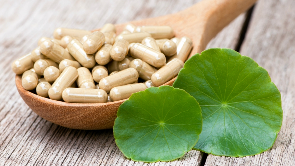 Gotu kola leaves next to supplements in a wooden spoon