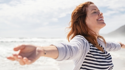 woman on beach strengthening lungs by breathing salty sea air