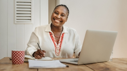 Smiling Black woman working on a laptop and writing notes while sitting at a desk in her home office