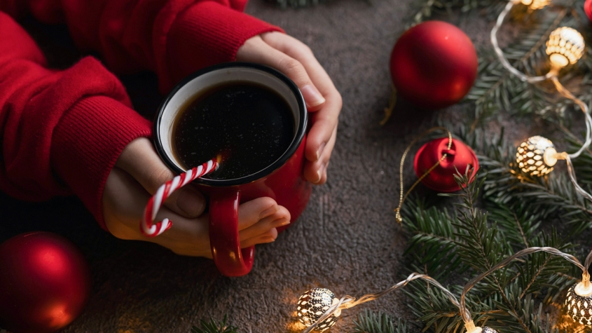 Hands holding mug with holiday lights