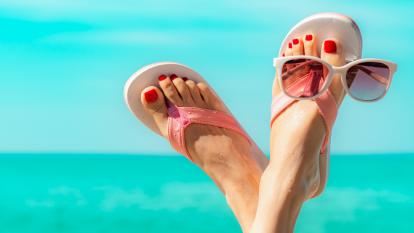 feet wearing flip flops at the beach