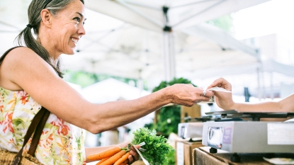 A smiling, older woman in her fifties shopping in a local farmers market with fresh, organic vegetables. She hands over money for a transaction to a vendor. She smiles as she buys carrots. Horizontal image with copy space.