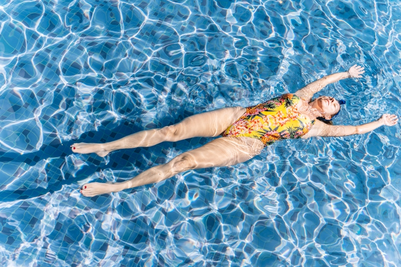 Woman in a swimsuit floating in a blue pool on a sunny day
