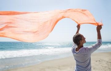 Senior woman standing on beach holding scarf