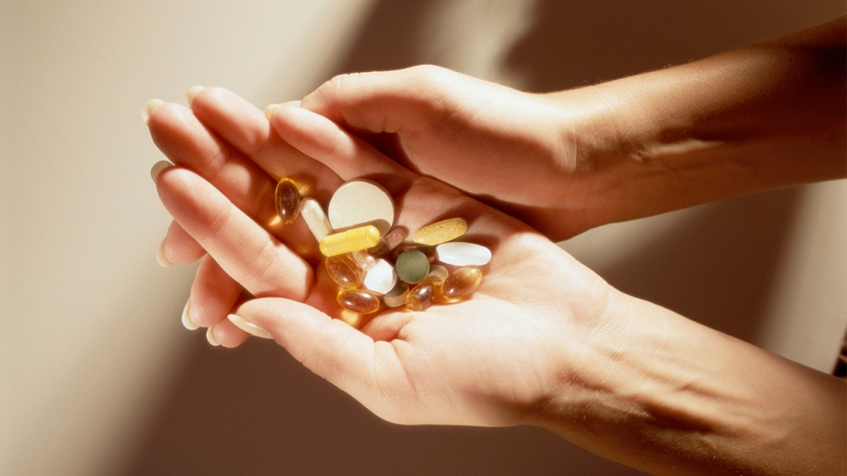 Woman holding vitamins_supplements