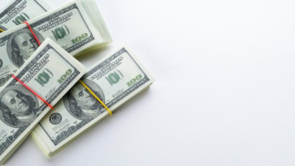 Us Dollars US Bills in Bundles On a White Background.