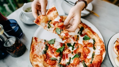 Woman picking up a slice of pizza