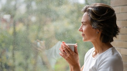 Woman drinking a cup of coffee while looking out of the window
